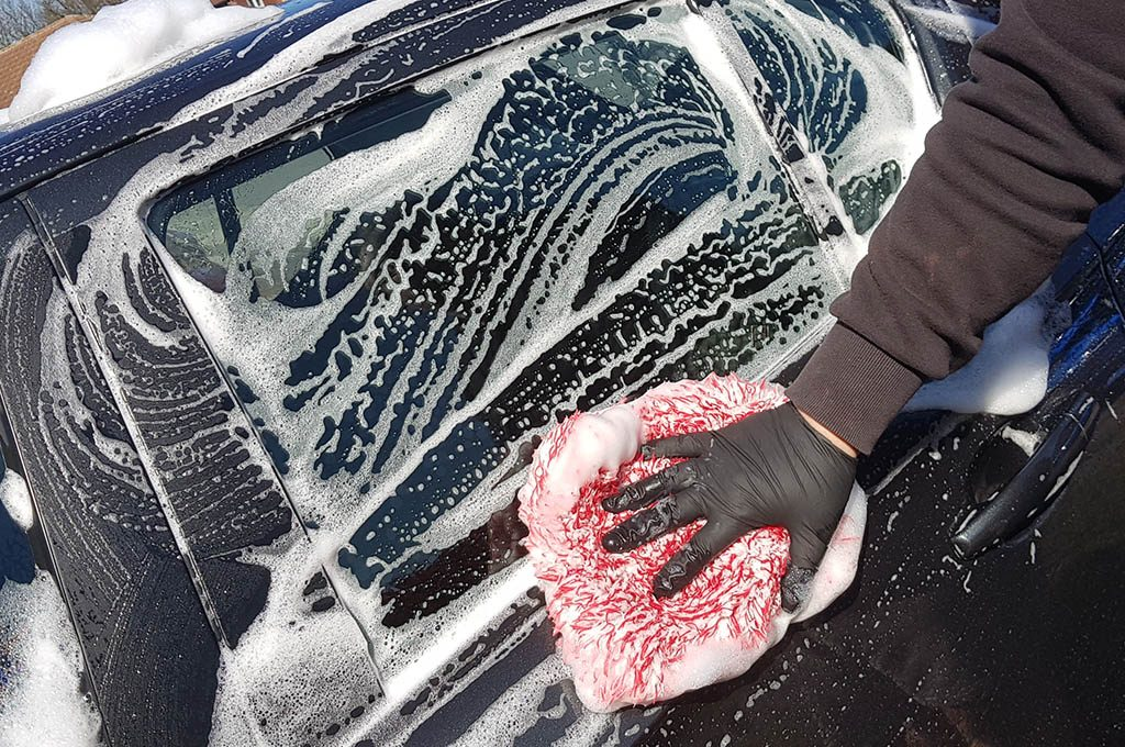 cleaning car with shampoo and washmitt
